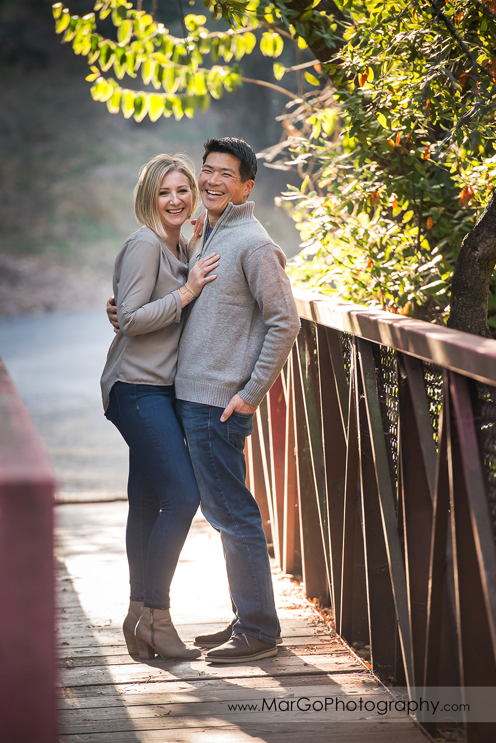 couple in gray shirts and jeans standing on the bridge at Carlos Bee Park in Hayward