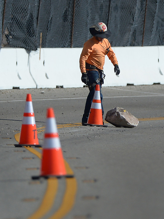 . A CalTrans worker moves a boulder that fell onto PCH during a scaling project, Monday, November 25, 2013, to dislodge potentially dangerous rocks on a hillside south of Pt. Mugu that was burnt during the Springs Fire last May. A steel mesh netting will be placed over the hillside in a couple weeks. (Photo by Michael Owen Baker/L.A. Daily News)