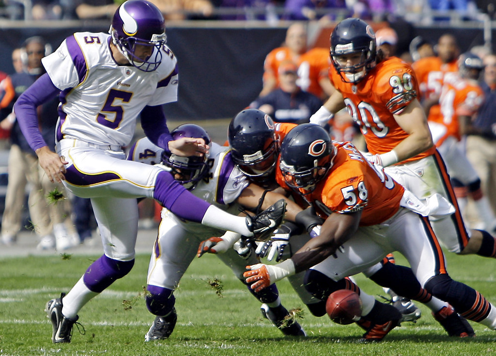 . Chicago\'s Joey LaRocque (90) and Darrell McClover (58) dive for the ball as Vikings punter Chris Kluwe attempts to kick the ball a second time, after he fumbled the snap and had his punt blocked, during the first quarter of an NFL football game, Sunday, Oct. 19, 2008, in Chicago. The Bears recovered the ball and scored a touchdown on the play. (AP Photo/M. Spencer Green)