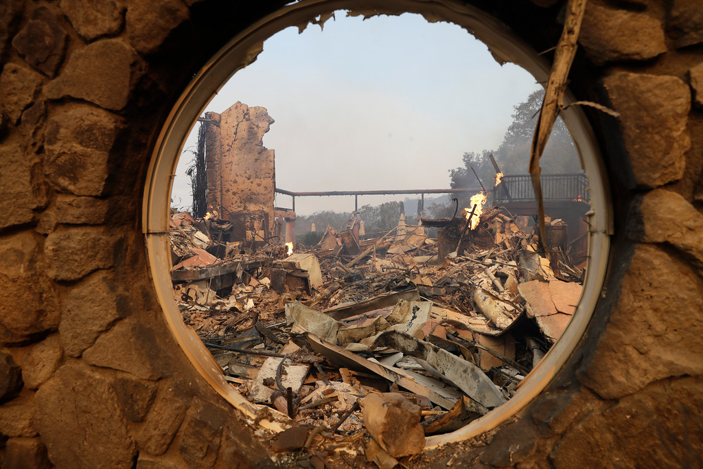 . The fire-ravaged Signorello Estate winery is seen through a window Monday, Oct. 9, 2017, in Napa, Calif. Wildfires whipped by powerful winds swept through Northern California sending residents on a headlong flight to safety through smoke and flames as homes burned.  (AP Photo/Marcio Jose Sanchez)