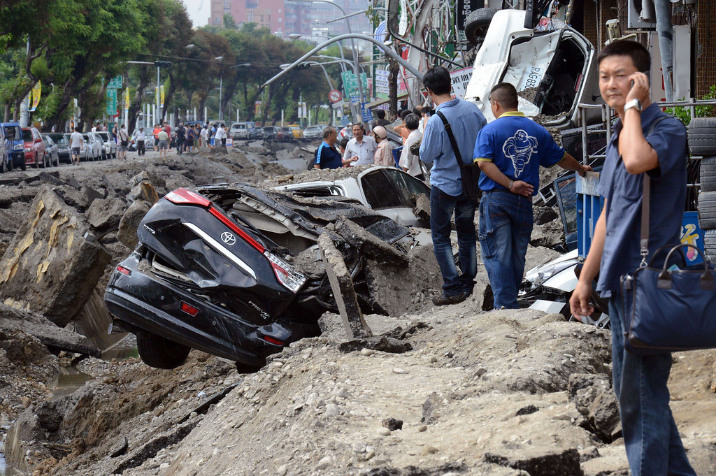 . Local residents look at the explosion site in southern Kaohsiung city on August 1, 2014.  A series of powerful gas blasts killed at least 22 people and injured up to 270 in the southern Taiwanese city of Kaohsiung, overturning cars and ripping open roads, officials said.   AFP PHOTO / SAM  YEH/AFP/Getty Images