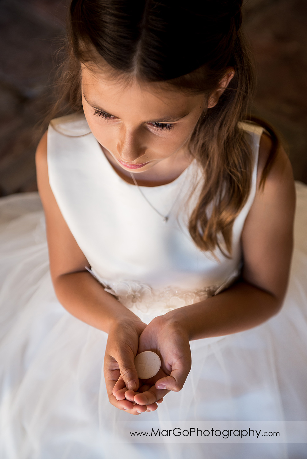 first communion girl in white dress holding wafer at Cafe Wisteria in Menlo Park