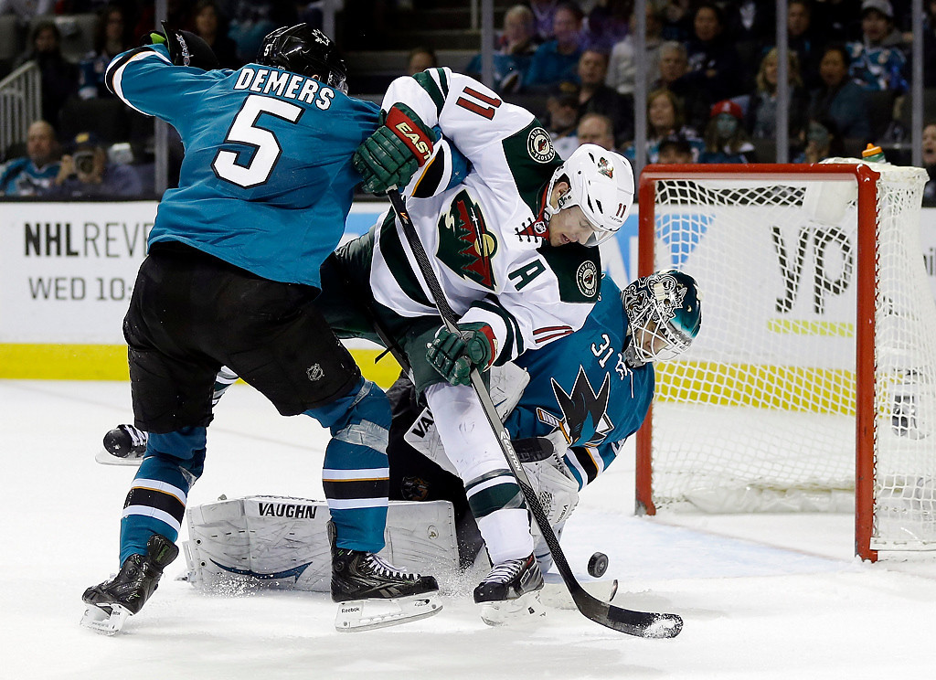 . Minnesota Wild\'s Zach Parise (11) collides with San Jose Sharks\' Jason Demers (5) and goalie Antti Niemi (31) of Finland, during the second period of an NHL hockey game on Saturday, Jan. 25, 2014, in San Jose, Calif. (AP Photo/Marcio Jose Sanchez)