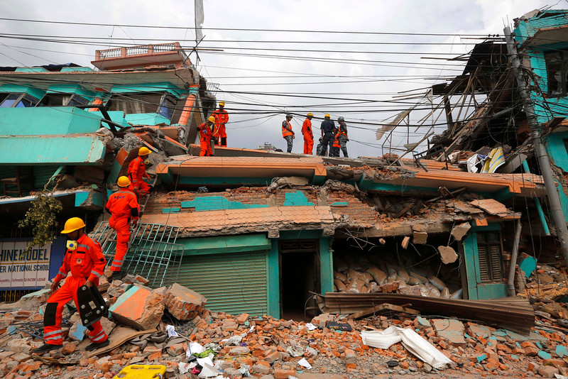 . India\'s National Disaster Response Force personnel look for survivors in a building, in Kathmandu, Nepal, Sunday, April 26, 2015. Sleeping in the streets and shell-shocked, Nepalese cremated the dead and dug through rubble for the missing Sunday, a day after a massive Himalayan earthquake devastated the region and destroyed homes and infrastructure. (AP Photo/Manish Swarup)