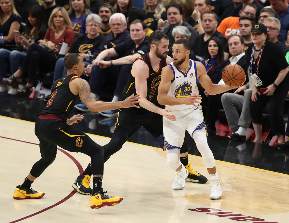 . Golden State Warriors\' Stephen Curry is defended by = Cleveland Cavaliers\' Kevin Love (0) and George Hill in the first half of Game 4 of basketball\'s NBA Finals, Friday, June 8, 2018, in Cleveland. (AP Photo/Carlos Osorio)