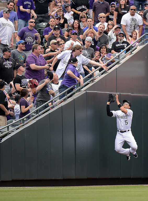 . Carlos Gonzalez (5) of the Colorado Rockies makes a leaping catch on a foul ball in the first inning against the San Diego Padres on Opening Day at Coors Field in Denver, Colorado on April 5, 2013. (Photo by Hyoung Chang/The Denver Post)