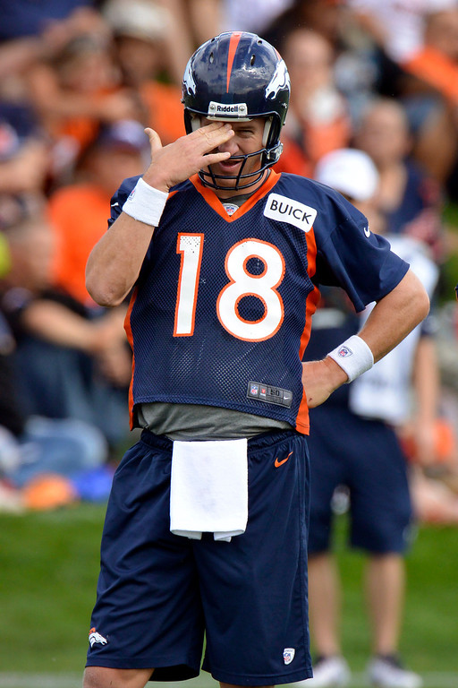 . Denver Broncos quarterback Peyton Manning (18) wipes the sweat from his brow during opening day of training camp July 25, 2013 at Dove Valley. (Photo By John Leyba/The Denver Post)