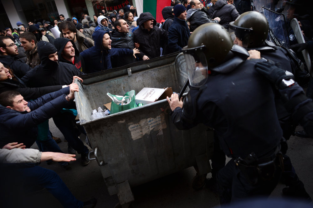 Description of . Demonstrators push a dumpster as they clash with riot police during a protest in downtown Sofia on February 17, 2013.  The protesters threw rocks, firecrackers, bottles, eggs and tomatoes at the police line manning the headquarters of Czech power producer CEZ and the president\'s office to protest against sky-high January electricity bills in the EU\'s poorest country, as the government drags its feet on liberalizing the energy market.    DIMITAR DILKOFF/AFP/Getty Images