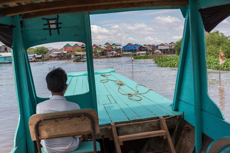 Rear view of man sitting on tourboat in Tonle Sap lake, Kampong Phluk, Siem Reap, Cambodia