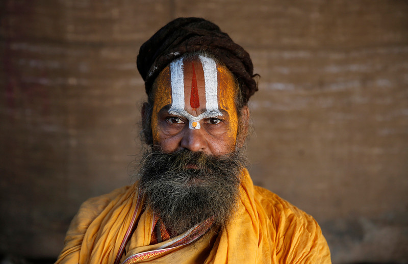 ". An Indian Sadhu looks into the camera as he participates in the \'Magh Mela\' festival at the ""Sangam,\"" the confluence of the Ganges and Yamuna,and mythical Saraswati river, in Allahabad, India,  Wednesday, Jan. 29, 2014. Hundreds of thousands of devout Hindus are expected to take holy dips at the confluence during the astronomically auspicious period of over 45 days celebrated as Magh Mela. (AP Photo/Rajesh Kumar Singh)"