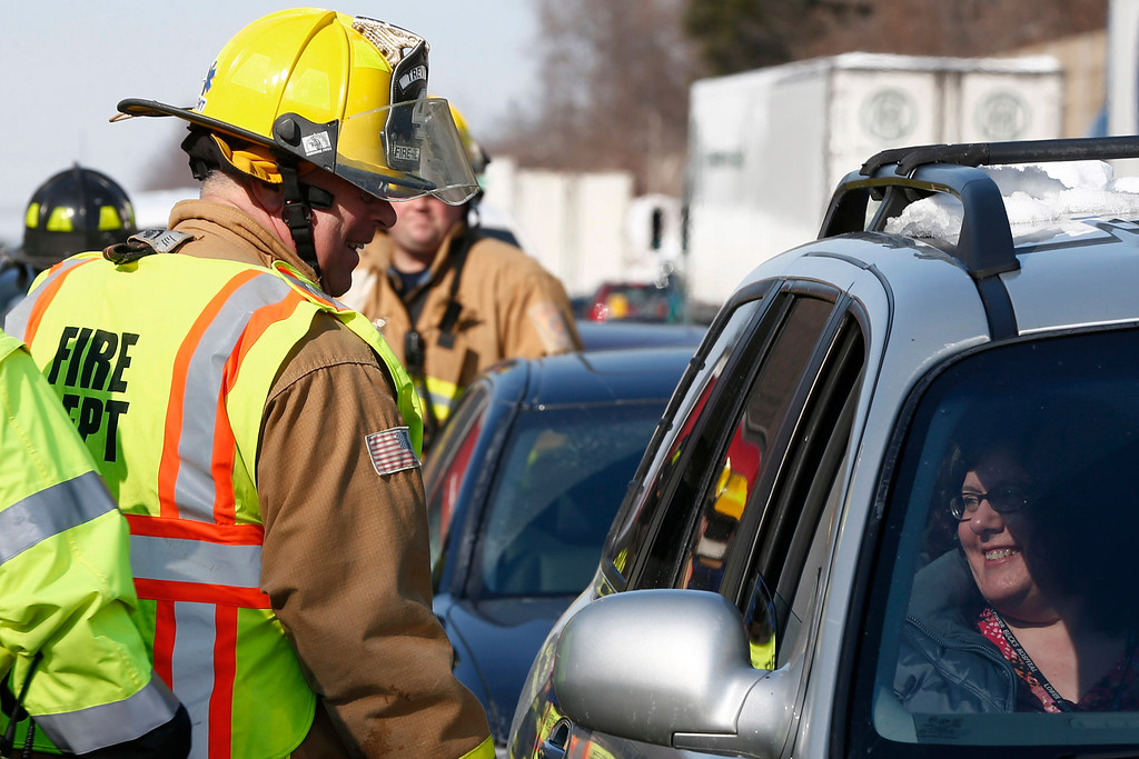 . A firefighter checks in on motorist in one of many vehicles involved in pile up accident, Friday, Feb. 14, 2014, in Bensalem, Pa. Traffic accidents involving multiple tractor trailers and dozens of cars have completely blocked one side of the Pennsylvania Turnpike outside Philadelphia and caused some injuries. (AP Photo/Matt Rourke)