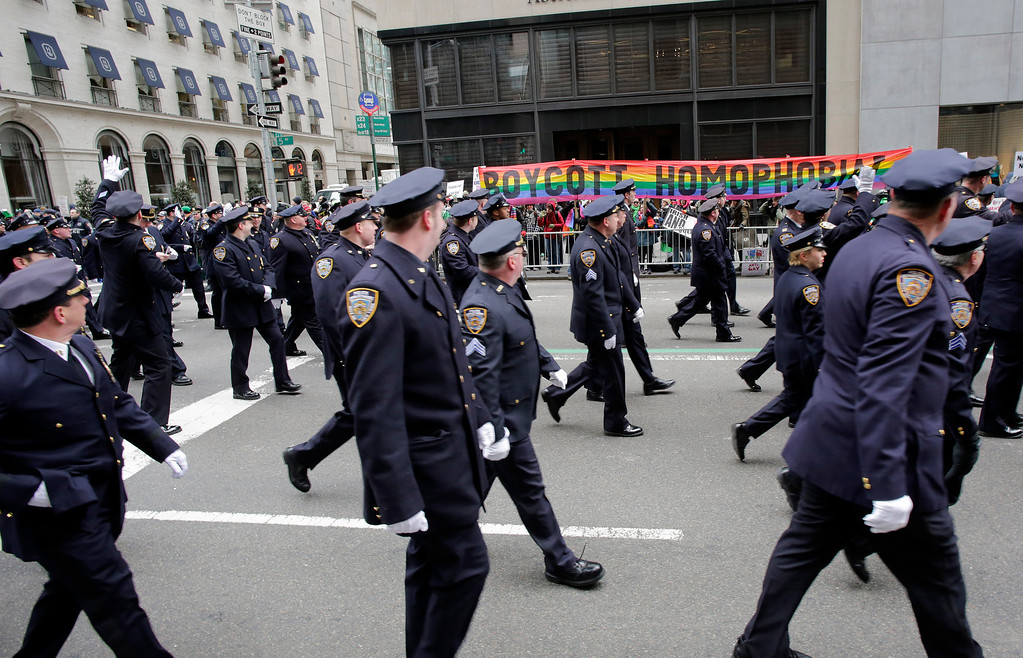 """. Members of the New York City Police Department march in the St. Patrick\'s Day parade past protesters, Monday, March 17, 2014 in New York. The banner reads \""""Boycott Homophobia.\""""  (AP Photo/Mark Lennihan)"""