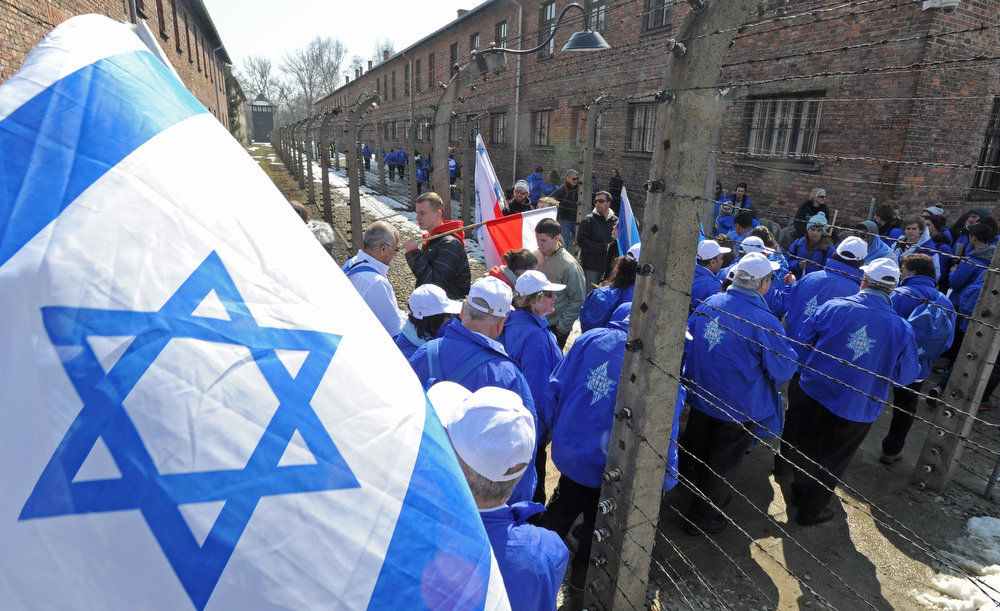 . Participants of the March of the Living walk through a barbed wire fence in the former Nazi Death Camp Auschwitz Birkenau in Oswiecim, Poland, Monday, April 8, 2013. Jews from Israel and around the world took part in the annual March of the Living on the 3km route from Auschwitz to Birkenau Nazi Death Camps, commemorating the Holocaust victims. (AP Photo/Alik Keplicz)