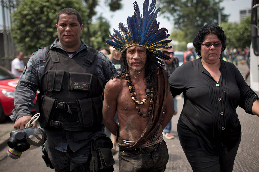 . An indigenous man is arrested during clashes outside the old Indian museum, a complex that has been occupied by Indians for years, during an eviction in Rio de Janeiro, Friday, March 22, 2013. Police in riot gear invaded an old Indian museum complex Friday and pulled out a few dozen indigenous people who for months resisted eviction from the building, which will be razed as part of World Cup preparations next to the legendary Maracana football stadium. (AP Photo/Felipe Dana)