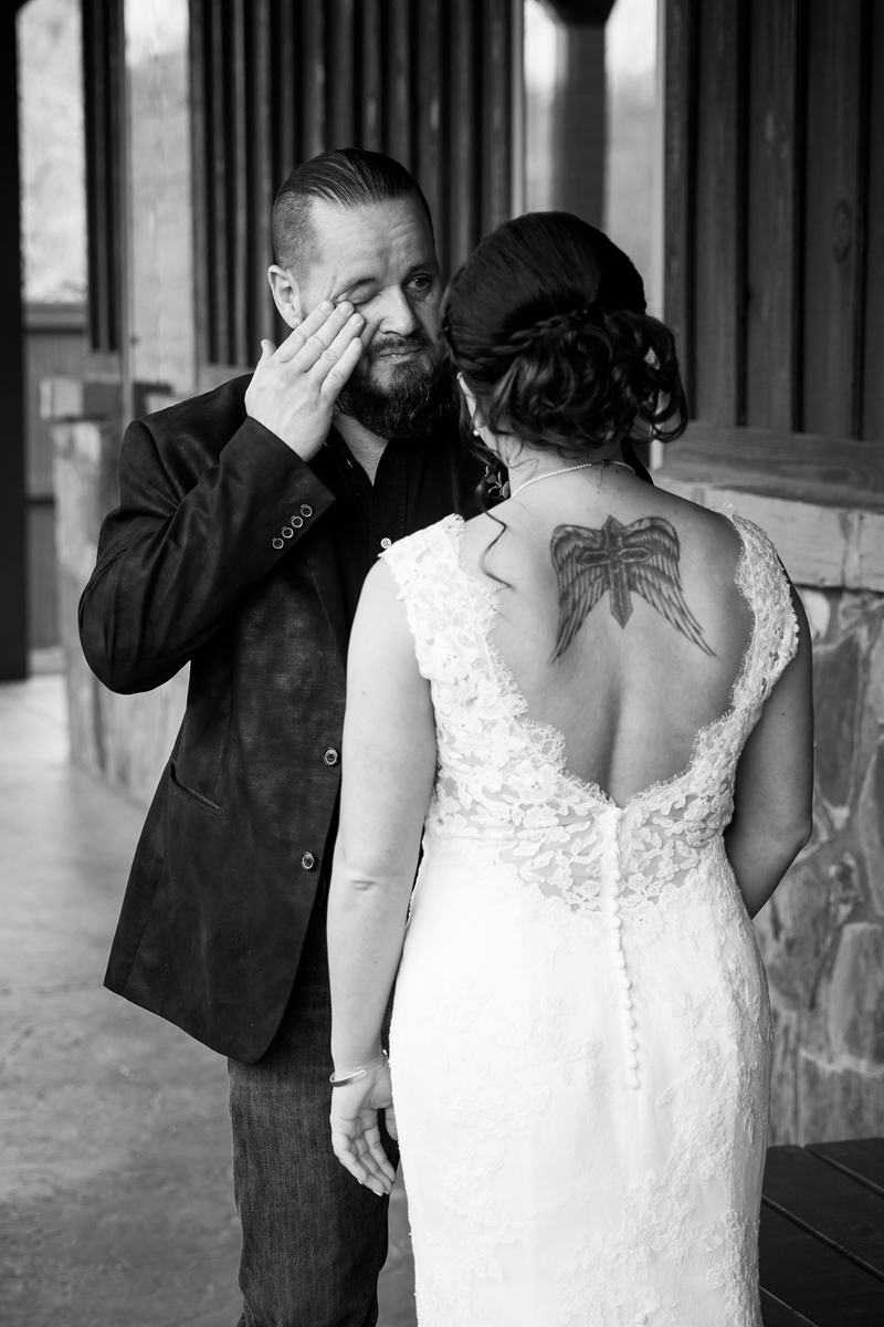 a groom wipes a tear from his eye as he sees his bride for the first time