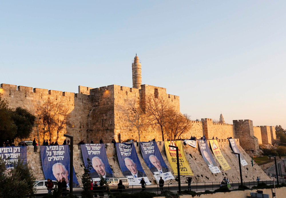 ". Campaign banners depicting Israel\'s Prime Minister Benjamin Netanyahu are seen after Likud-Yisrael Beitenu activists draped them on walls surrounding Jerusalem\'s Old City January 20, 2013. Netanyahu said on Saturday a country with as many enemies as Israel cannot afford a weak ruling party, after polls ahead of Tuesday\'s parliamentary election showed a slide in his support. The banners read (L and C) ""Only Netanyahu will protect Jerusalem\"" and \""Warning! \'67 borders ahead\"". REUTERS/Ronen Zvulun"