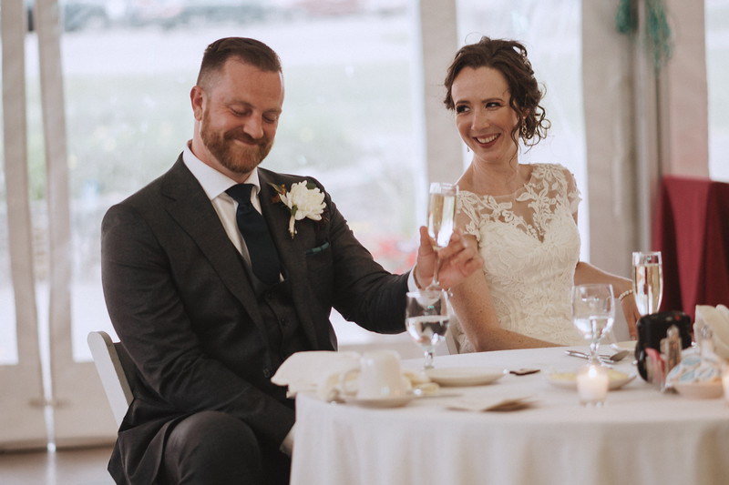 The groom smiles as he raises a champagne glass while the bride laughs at him.