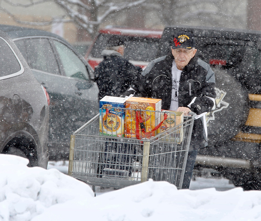 . Bob Kist of Mars, Pa. pushes his shopping cart of groceries to his car in the snowy store parking lot on Monday, Jan. 26, 2015 in Cranberry, Butler County, Pa. The Philadelphia-to-Boston corridor of more than 35 million people began shutting down and bundling up Monday against a potentially history-making storm that could unload a paralyzing 1 to 3 feet of snow.  (AP Photo/Keith Srakocic)