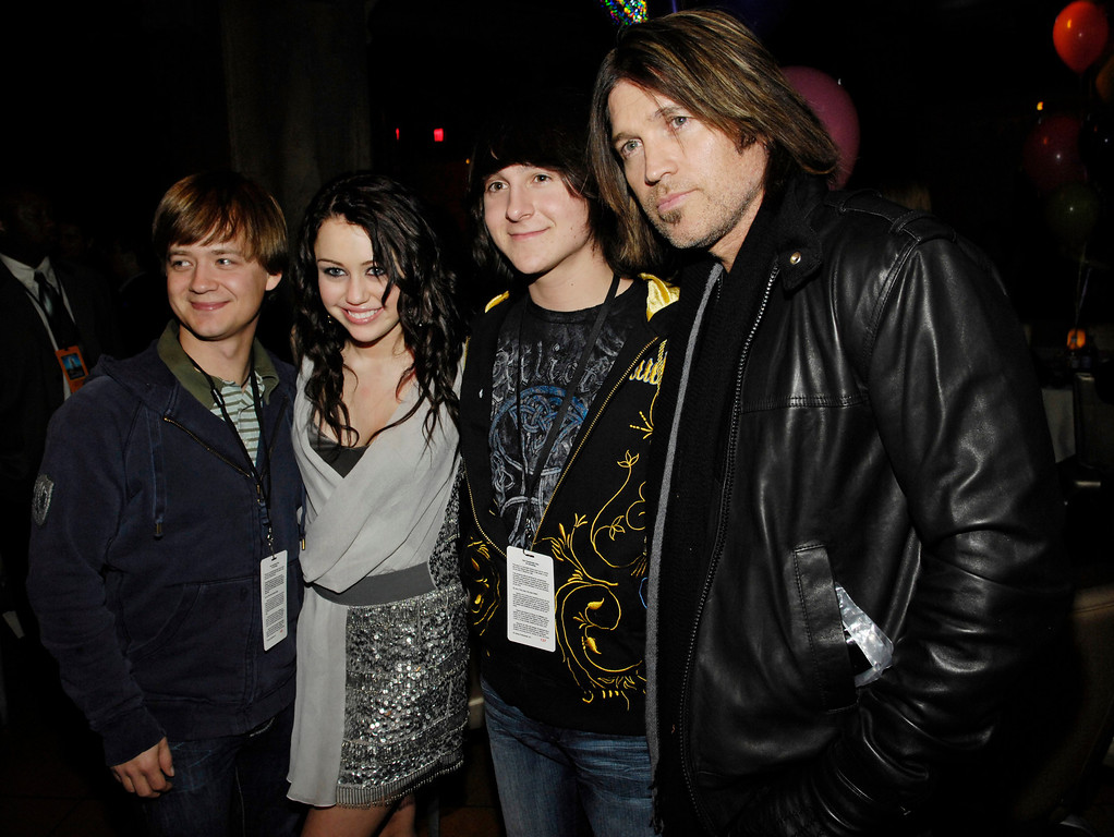""". Actress/singer Miley Cyrus, second from left, poses with fellow \""""Hannah Montana\"""" cast members (L-R) Jason Earles, Mitchel Musso and her father Billy Ray Cyrus at the world premiere of the film \""""Hannah Montana & Miley Cyrus: Best of Both Worlds Concert\"""" in Los Angeles, Thursday, Jan. 17, 2008. (AP Photo/Chris Pizzello)"""