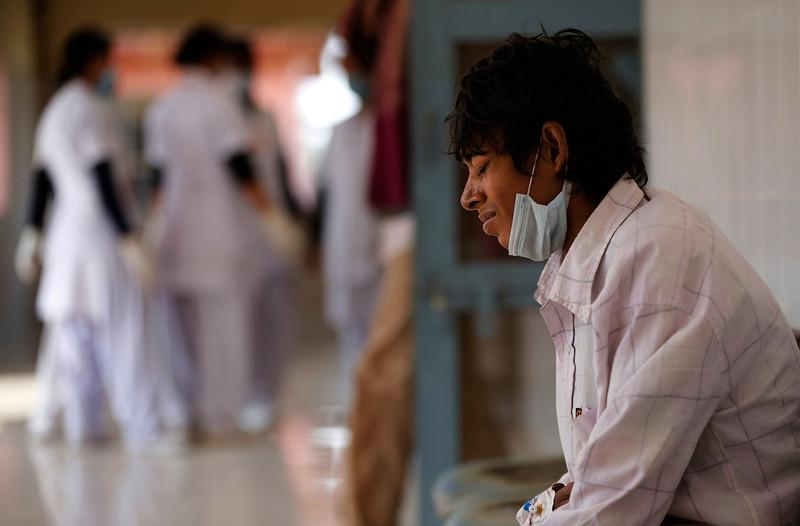 . In this Monday, Feb. 3, 2014 photo, a tuberculosis patient Manjeet Mishra, 18, sits outside a ward at Lal Bahadur Shastri Government Hospital at Ram Nagar in Varanasi, India. (AP Photo/Rajesh Kumar Singh)
