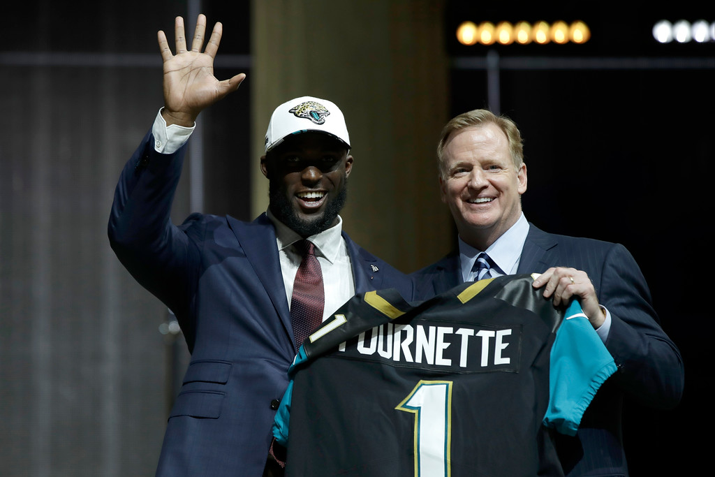. LSU\'s Leonard Fournette, left, waves as he poses with NFL commissioner Roger Goodell after being selected by the Jacksonville Jaguars during the first round of the 2017 NFL football draft, Thursday, April 27, 2017, in Philadelphia. (AP Photo/Matt Rourke)