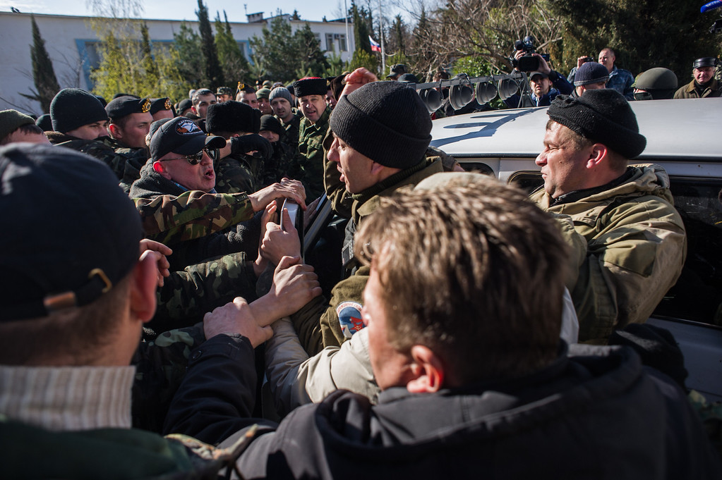 . Crimean pro-Russian self-defense forces scuffle with Ukrainian servicemen outside the Ukrainian navy headquarters in Sevastopol, Crimea, Wednesday, March 19, 2014.  (AP Photo/Andrew Lubimov)