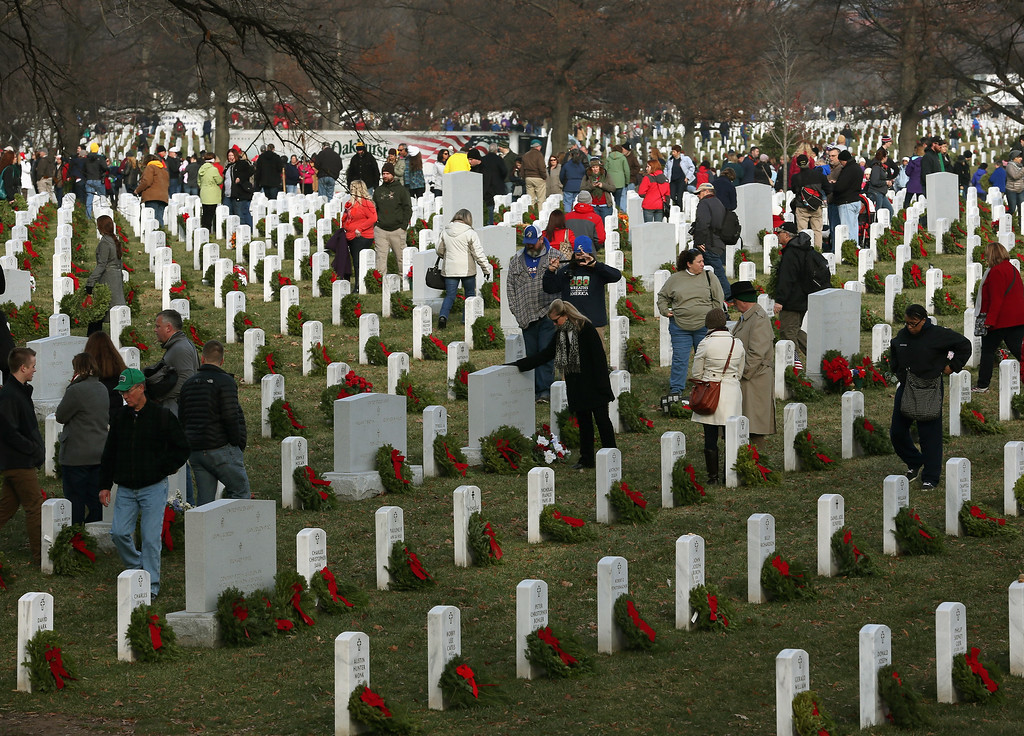 . Volunteers gather in Section 60 to place wreaths on graves during the National Wreaths Across America Day at Arlington National Cemetery, December 13, 2014 in Arlington, Virginia. Volunteers placed wreaths throughout the entire cemetery in honor of Arlington\'s 150th anniversary.  (Photo by Mark Wilson/Getty Images)