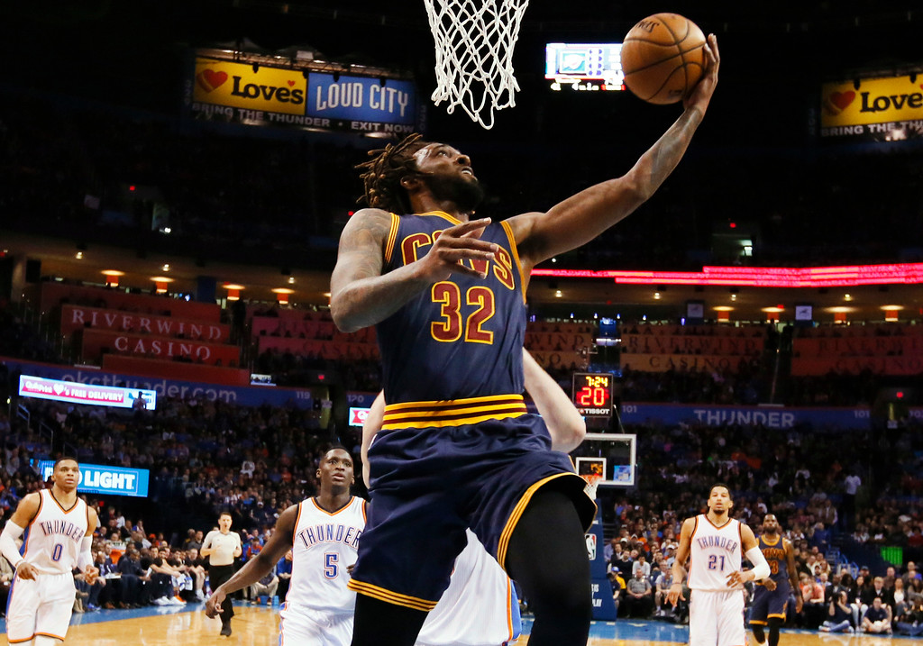 . Cleveland Cavaliers forward Derrick Williams (32) shoots in front of Oklahoma City Thunder guard Russell Westbrook (0), guard Victor Oladipo, and forward Andre Roberson (21) during the second quarter of an NBA basketball game in Oklahoma City, Thursday, Feb. 9, 2017. (AP Photo/Sue Ogrocki)