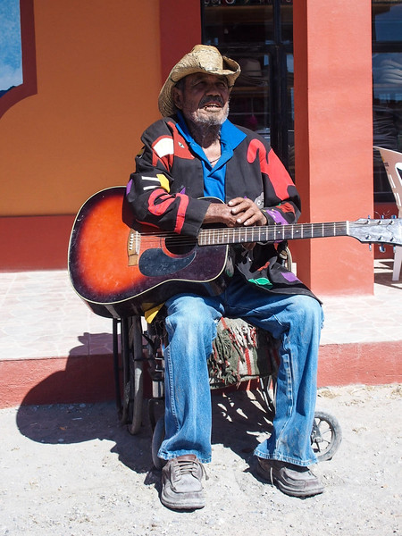 Playing his guitar for tips in front of Jose Falcon's restaurant.