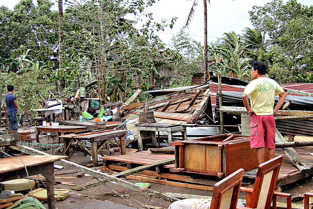 Description of . A man looks at his damaged house destroyed by strong winds brought about by Typhoon Bopha in Butuan City, Agusan del Sur, in southern island of Mindanao on December 4, 2012. Typhoon Bopha killed at least eight people in the Philippines on December 4, and there were fears the toll could rise sharply as the strongest storm to hit the country this year brought scenes of devastation.  ERWIN MASCARINAS/AFP/Getty Images