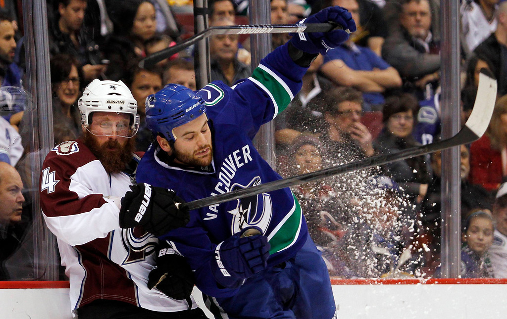 . Vancouver Canucks Zack Kassian (R) checks Greg Zanon of the Colorado Avalanche during the first period of their NHL hockey game in Vancouver, British Columbia January 30, 2013.   REUTERS/Ben Nelms