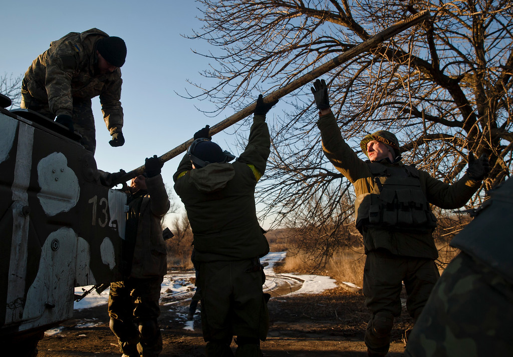 . Ukrainian servicemen prepare to tow a broken down military vehicle outside Artemivsk, Ukraine, while pulling out of Debaltseve, Wednesday, Feb. 18, 2015. After weeks of relentless fighting, the embattled Ukrainian rail hub of Debaltseve fell Wednesday to Russia-backed separatists, who hoisted a flag in triumph over the town. The Ukrainian president confirmed that he had ordered troops to pull out and the rebels reported taking hundreds of soldiers captive.(AP Photo/Vadim Ghirda)
