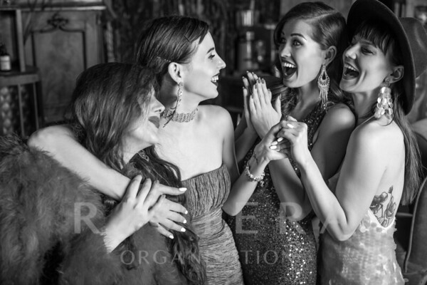 Group of young laughing stylish girls dressed classical style in interior of luxury club. Black-white photo.