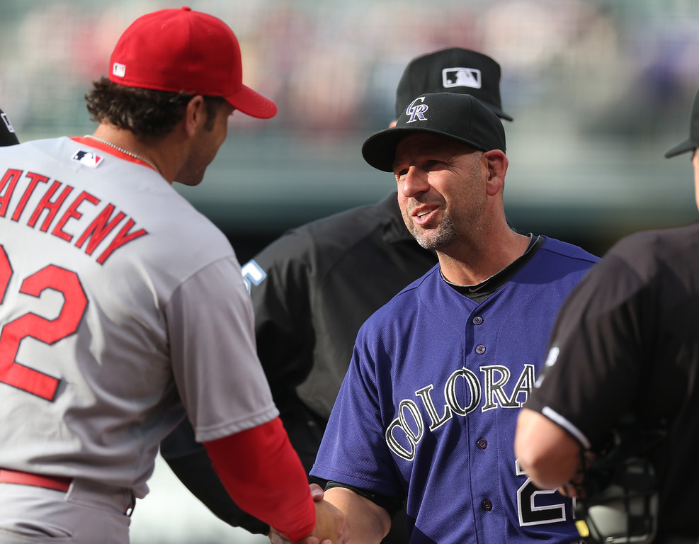 . Colorado Rockies manager Walt Weiss, right, greets St. Louis Cardinals manager Mike Matheny as they exchange lineup cards at home plate before the Rockies host the Cardinals in the first inning of a baseball game in Denver on Monday, June 23, 2014. (AP Photo/David Zalubowski)
