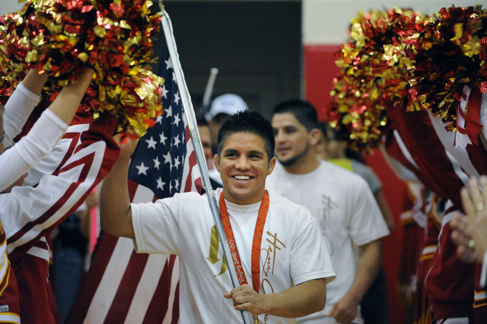 Description of . Holding a large American flag, Henry Cejudo arrives in the gymnasium to the music from the soundtrack of Rocky and the school's cheerleaders. 2006, Coronado High School graduate Heny Cejudo made a triumphant return to Colorado Springs to his old alma mater.  This was his first visit back to Colorado since capturing the gold medal in free style wrestling at the 2008 Beijing Summer Olympic Games.  Cejudo was a two-time Colorado State wrestling champion while attending Coronado High School.  He was undefeated as Colorado prep, and is widely known as one of the greatest high school wrestlers in American history.  Cejudo became the youngest American ever (21 years old) to win an Olympic gold medal in freestyle wrestling  (55kg weight class.) To honor Cejudo's homecoming, Coronado High School held a school wide assembly in the main gym.  The assembly gave students the opportunity to celebrate the gold medal performance with Henry and at the same time, allowing Coronado to honor Cejudo for his outstanding accomplishment. (Helen H. Richardson/The Denver Post)