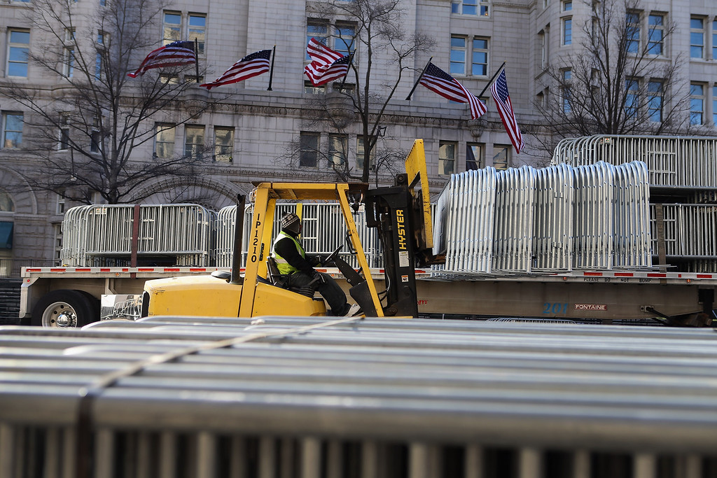 . A worker moves security fences into position along Pennsylvania Ave as preparations continue for the Inauguration Parade on January 20, 2013 in Washington, DC.  The US capital is preparing for the second inauguration of US President Barack Obama, which will take place on January 21.  (Photo by Joe Raedle/Getty Images)
