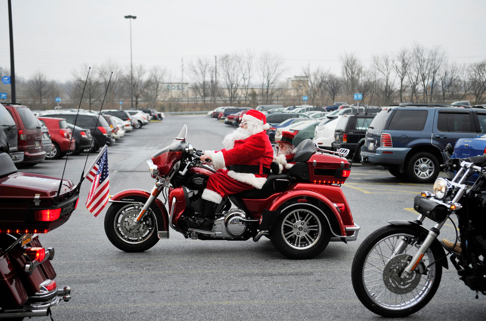". In this photo taken on Saturday, Dec. 8, 2012 Roger Kessler of Dover Township stalls his motorcycle in a parade of other Santa Claus-garbed motorcyclists riding through the Wal-mart  in West Manchester Township, Pa. ""Spreading the Cheer\"" is a group of motorcyclists who dress up as Santa Claus and elves and ride throughout York County to make people smile wherever they show up. (AP Photo/York Daily Record/Sunday News, Chris Dunn)"