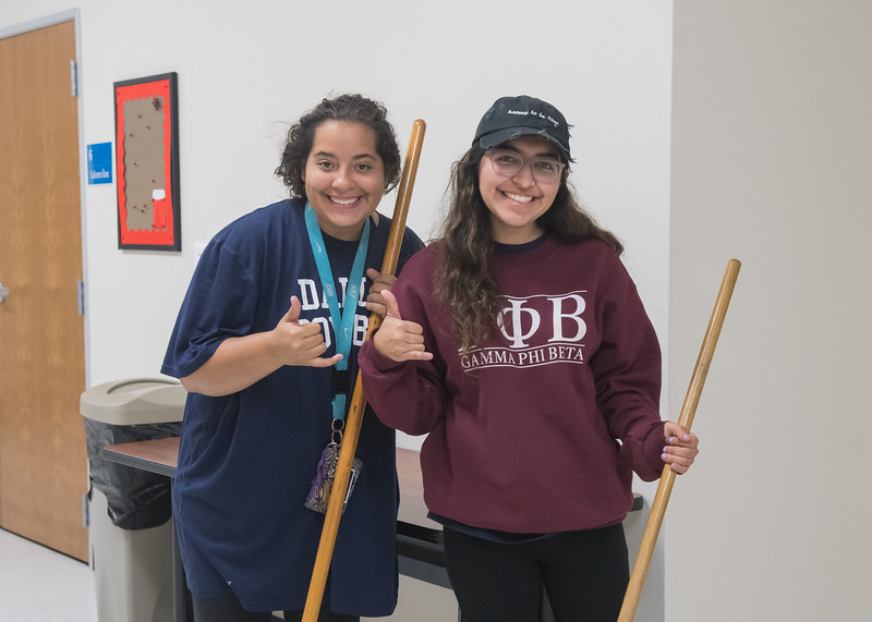 Brittany Harper (Left) and Taylor Savcedo take a quick break from mopping the Deaf and Hard of Hearing Center floors to show islander pride during The BIG Event.