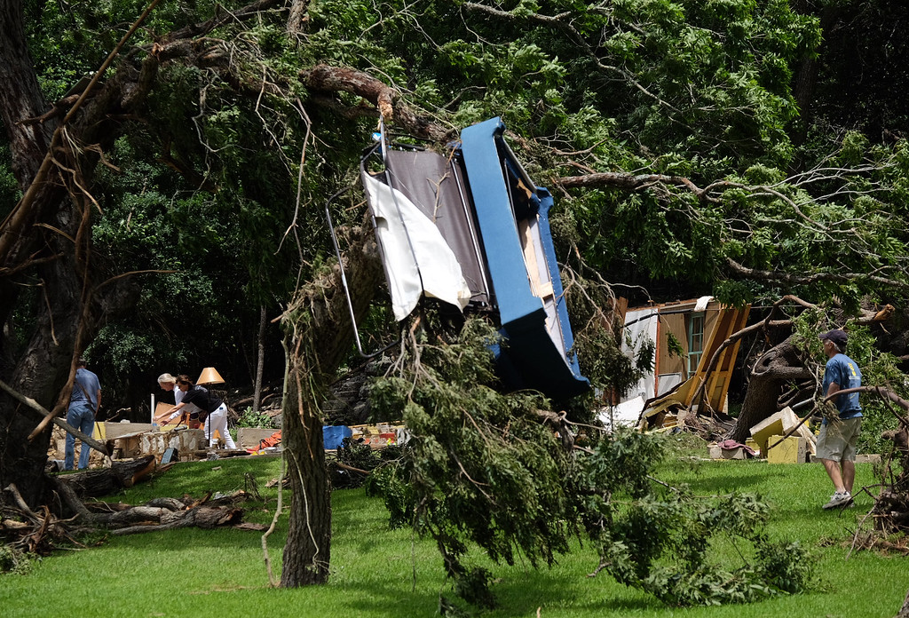 . A couch hangs in a tree as people search for possessions after a flash flood along the Blanco River, Monday, May 25, 2015, in Wimberley, Texas. Several people were reported missing in flash flooding from a line of storms that stretched from the Gulf of Mexico to the Great Lakes. (Rodolfo Gonzalez/Austin American-Statesman via AP)