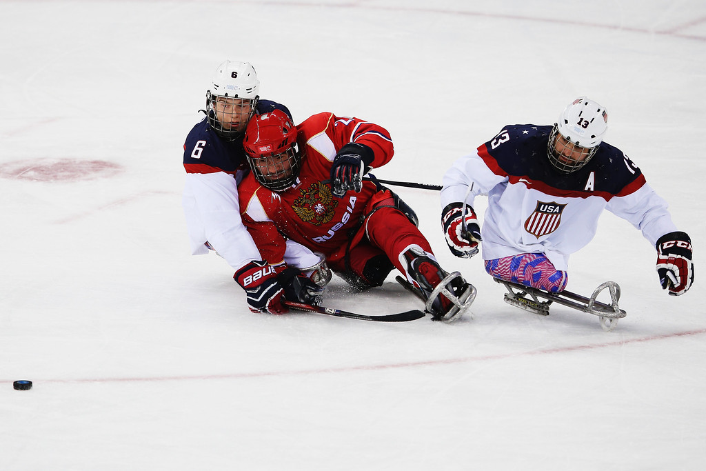 . Declan Farmer of the USA and Joshua Sweeney of the USA defends against Evgeny Petrov of Russia  during the ice sledge hockey gold medal game between the Russian Federation and the United States of America at the Shayba Arena during day eight of the 2014 Paralympic Winter Games on March 15, 2014 in Sochi, Russia.  (Photo by Hannah Peters/Getty Images)