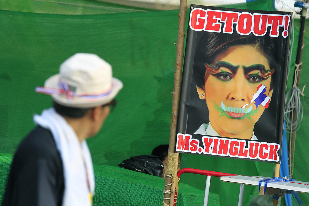 . A Thai anti-government protester walks past a poster against caretaker Prime Minister Yingluck Shinawatra at a protest site in Chaengwattana road, Bangkok, Thailand, 18 February 2014. EPA/NARONG SANGNAK
