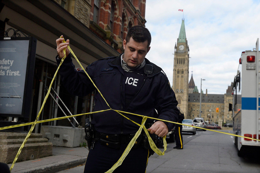 . Police cordon off a street leading to Parliament Hill in Ottawa on Wednesday Oct. 22, 2014.  A soldier standing guard at the National War Memorial has been shot by an unknown gunman and there have been reports of gunfire inside the halls of Parliament. (AP Photo/The Canadian Press, Adrian Wyld)