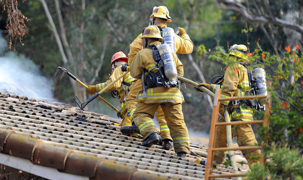 . Los Angeles County Firefighters vent a roof of a single family home that was damaged by a fire. The fire started in the garage along the 1300 block of Via Verde. No injuries, but 5 cars were destroyed including two jaguars in San Dimas, Calif., on Saturday, Jan.4, 2014. 