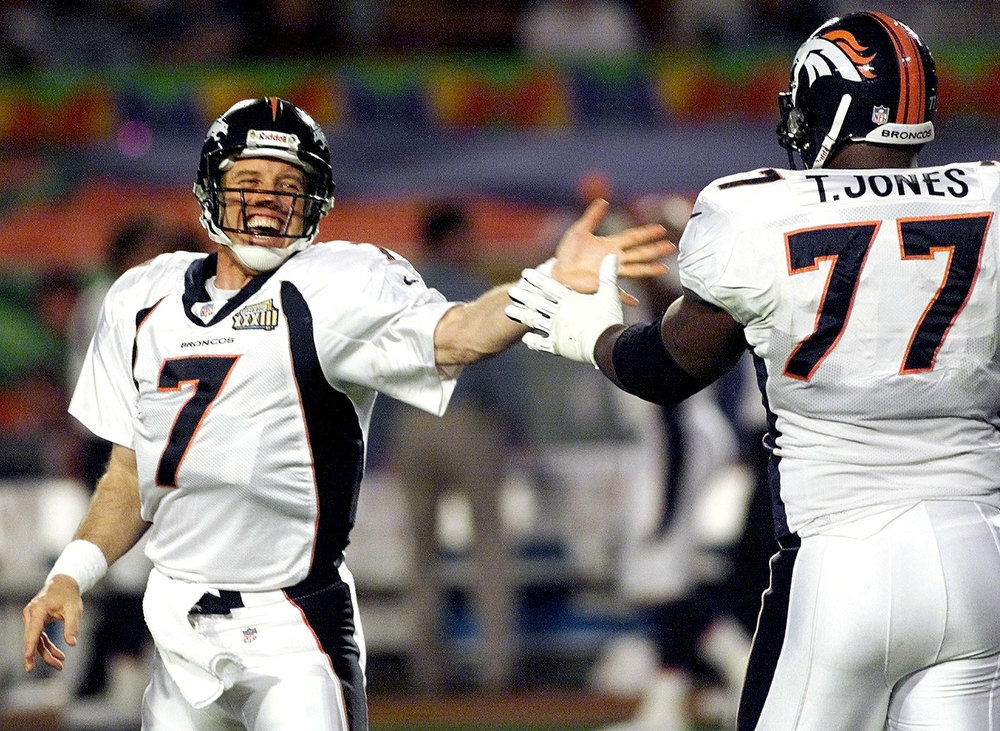 Description of . Denver Broncos quarterback John Eway (L) slaps hands with tackle Tony Jones after the Broncos scored on an 80-yard touchdown pass play in first half action against the Atlanta Falcons during Super Bowl XXXIII, January 31, 1999 at Pro Player Stadium in Miami, Florida. TIM CLARY/AFP/Getty Images