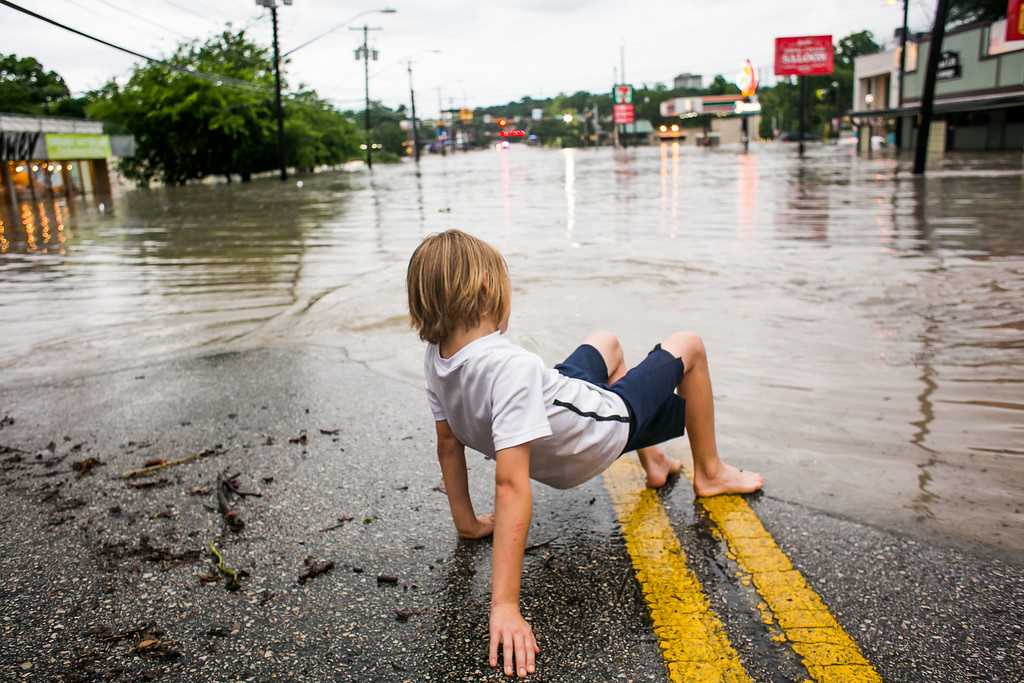 . AUSTIN, TX - MAY 25:   Murphy Canning plays near a street that remains underwater from days of heavy rain on May 25, 2015 in Austin, Texas. Texas Gov. Greg Abbott toured the damage zone where one person is confirmed dead and at least 12 others missing in flooding along the Rio Blanco, which reports say rose as much as 40 feet in places, caused by more than 10 inches of rain over a four-day period. The governor earlier declared a state of emergency in 24 Texas counties.  (Photo by Drew Anthony Smith/Getty Images)