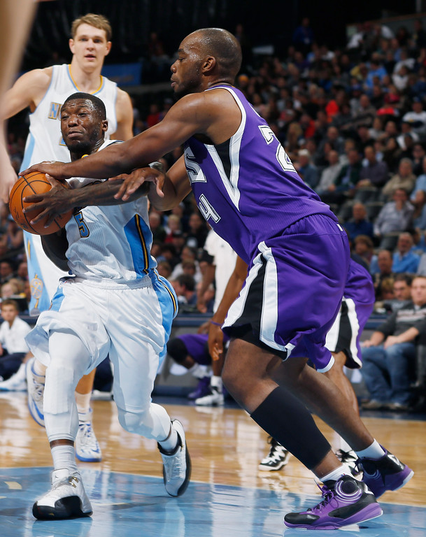 . Sacramento Kings forward Carl Landry, right, strips the ball from Denver Nuggets guard Nate Robinson as he drives the lane in the second half of the Kings\' 110-105 victory in an NBA basketball game in Denver on Monday, Nov. 3, 2014. (AP Photo/David Zalubowski)