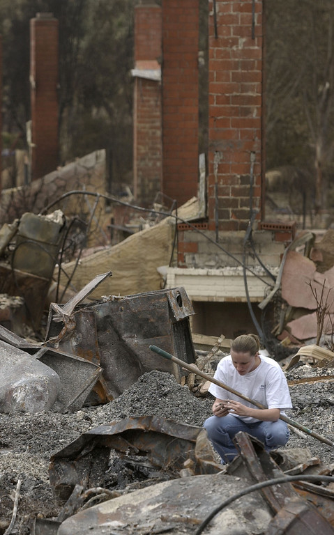 . Rebecca Mitchell looks through rubble as she helps salvage items from a friend\'s home in the Scripps Ranch area of San Diego, Calif. Thursday, Oct. 30, 2003. The home was among more than 1,500 lost in the 275,000 acre Cedar fire. (AP Photo/Charlie Riedel)