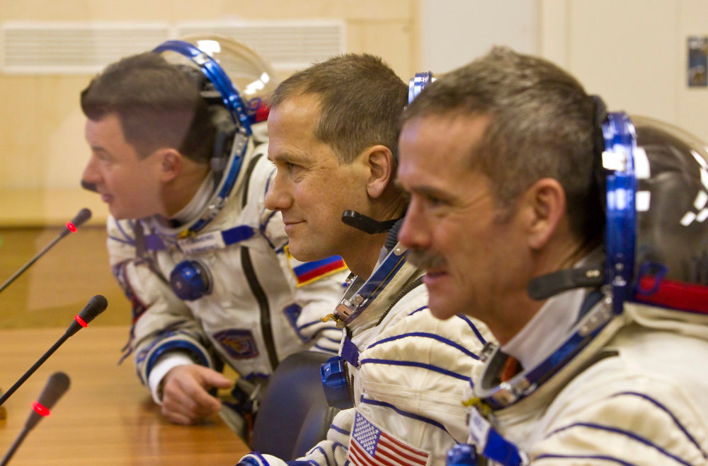 Description of . The International Space Station (ISS) crew members, from left: Russian cosmonaut Roman Romanenko, U.S. astronaut Thomas Marshburn and Canadian astronaut Chris Hadfield speak with relatives after putting on their space suits at the Baikonur cosmodrome Kazakhstan  Wednesday, Dec. 19, 2012.  (AP Photo/ Shamil Zhumatov, pool)