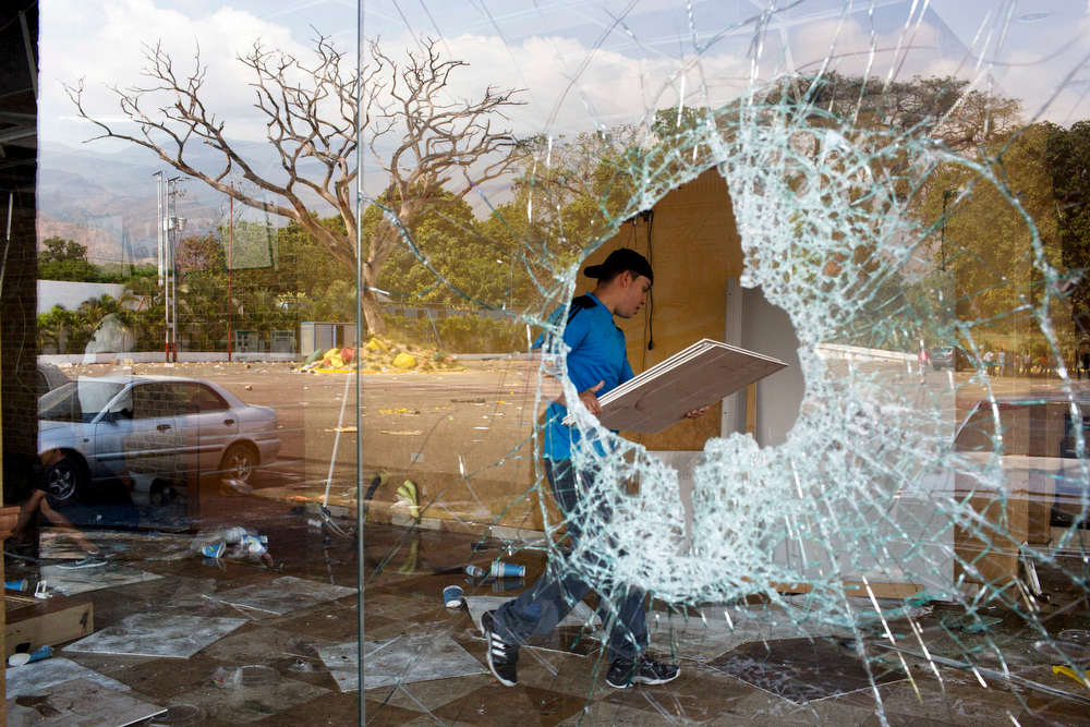 . A worker cleans up what remains a Subway sandwich shop at the looted SuperLider commercial center in Maracay, Venezuela, Wednesday, Feb. 26, 2014. People looted the commercial center starting Monday night, after almost two weeks of protests that began with students and were soon joined by others in several cities, upset over crime, economic problems and heavy-handed government response to the protests. (AP Photo/Rodrigo Abd)