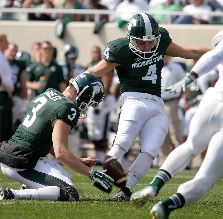 . Michigan State\'s Michael Geiger (4) kicks one of his 10 extra points as Mike Sadler (3) holds during the first quarter of an NCAA college football game against Eastern Michigan, Saturday, Sept. 20, 2014, in East Lansing, Mich. Geiger was perfect on 10 extra points and one field goal. Michigan State won 73-14. (AP Photo/Al Goldis)